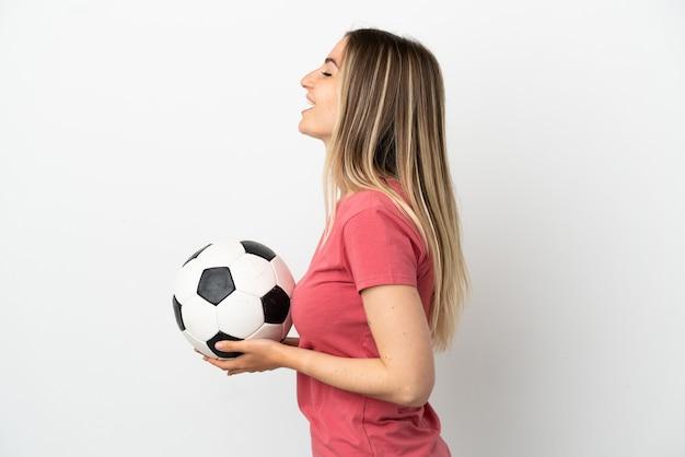 Młoda kobieta piłkarz nad odosobnioną białą ścianą śmiejącą się w pozycji bocznej