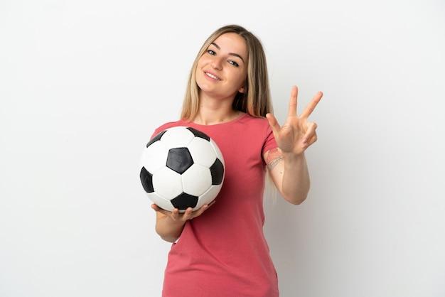 Młoda kobieta piłkarz nad odosobnioną białą ścianą szczęśliwa i licząca trzy palcami