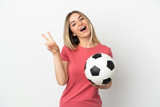 Młoda kobieta piłkarz nad odosobnioną białą ścianą uśmiecha się i pokazuje znak zwycięstwa