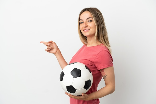 Młoda kobieta piłkarz nad odosobnioną białą ścianą, wskazując palcem w bok