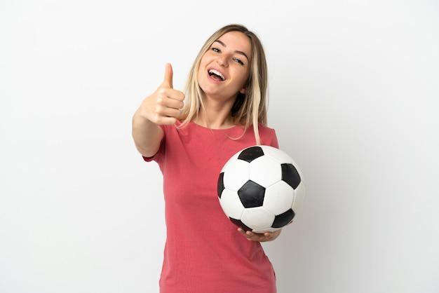 Młoda kobieta piłkarz nad odosobnioną białą ścianą z kciukami do góry, ponieważ wydarzyło się coś dobrego