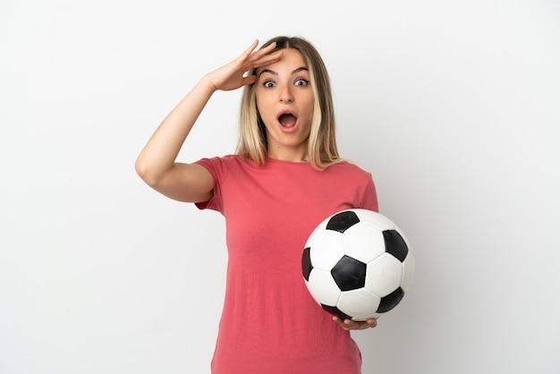 Młoda kobieta piłkarz nad odosobnioną białą ścianą z wyrazem zaskoczenia