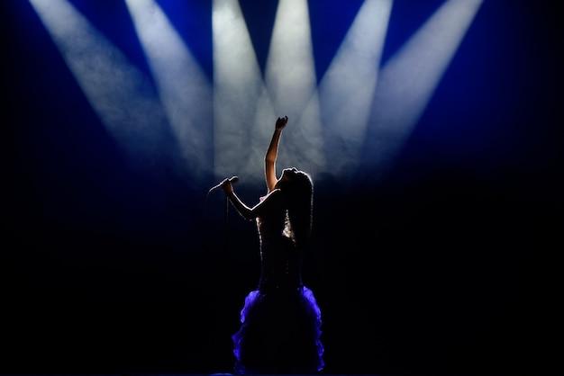 Młoda kobieta piosenkarka na scenie podczas koncertu.