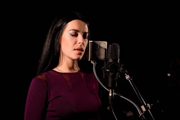 Młoda kobieta piosenkarka przed mikrofonem.