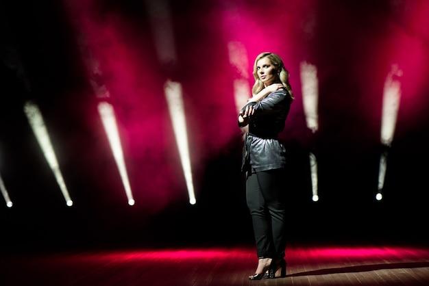 Młoda kobieta piosenkarka z kolorowymi światłami na koncercie