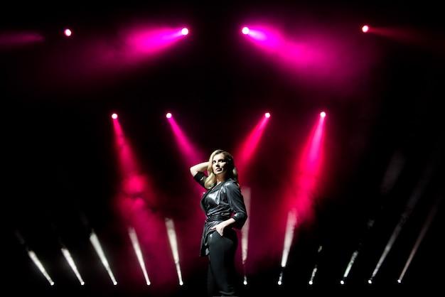 Młoda kobieta piosenkarz z kolorowymi światłami na koncercie