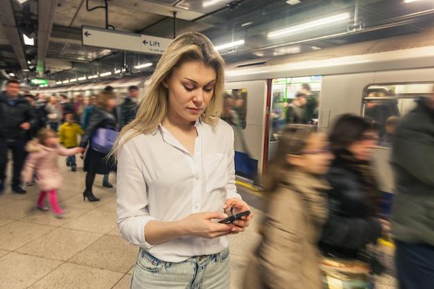 Młoda kobieta pisać na maszynie na mądrze telefonie przy stacją metru