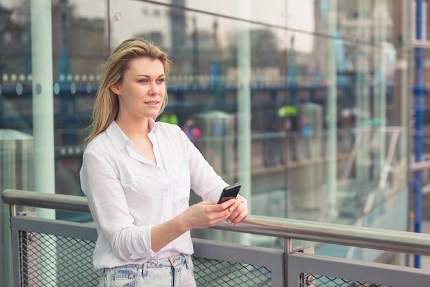 Młoda kobieta pisać na maszynie na mądrze telefonie