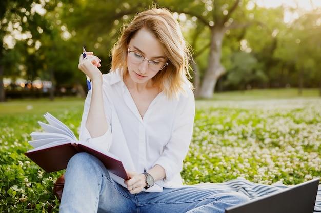 Młoda kobieta pisze coś w zeszycie w parku