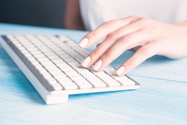 Młoda kobieta pisze na klawiaturze