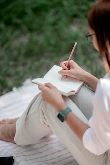 Młoda kobieta pisze na notatniku ołówkiem, siedząc na zewnątrz.