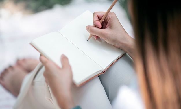 Młoda kobieta pisze na notatniku ołówkiem.