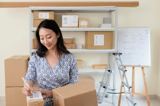 Młoda kobieta pisze szczegóły na pudełku dostawy
