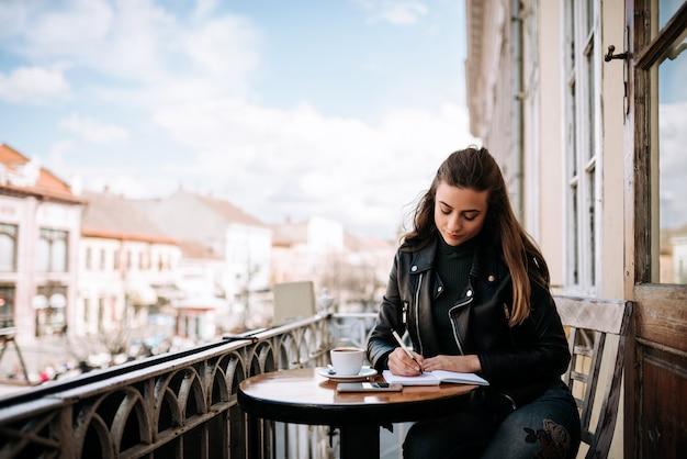 Młoda kobieta pisze w pamiętniku siedząc na tarasie w mieście.