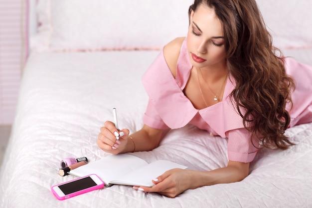 Młoda kobieta pisze w swoim dzienniku wolne miejsce.