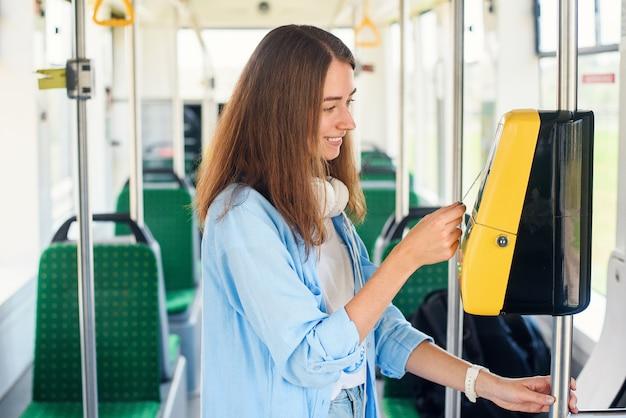 Młoda kobieta płaci kartą bankową za transport publiczny tramwajem lub metrem.
