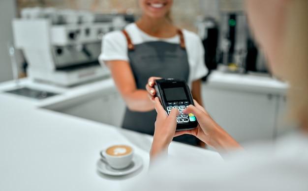 Młoda kobieta płaci kartą kredytową w kawiarni. kobieta wpisując pin bezpieczeństwa w czytnik kart kredytowych z kobieta barista stojący za ladą kasową w kawiarni.