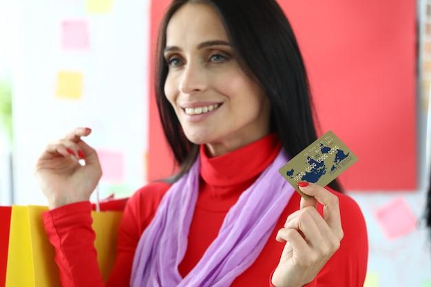 Młoda kobieta płaci za zakupy kartą kredytową