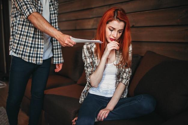 Młoda kobieta płacze, mężczyzna wychodzi z domu, kłótnia rodzinna, konflikt pary. problem w związku