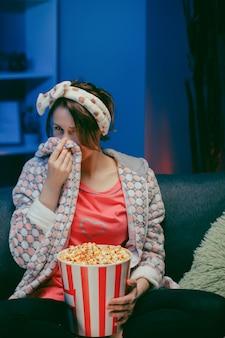Młoda kobieta płacze podczas oglądania bardzo poruszającego filmu z popcornem w nocy