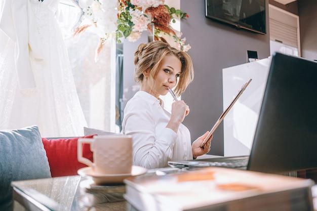 Młoda kobieta planowania ślubu w biurze z laptopa i tabletu do pisania