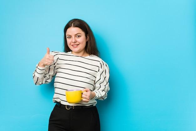 Młoda kobieta plus size trzyma kubek herbaty, uśmiechając się i podnosząc kciuk do góry