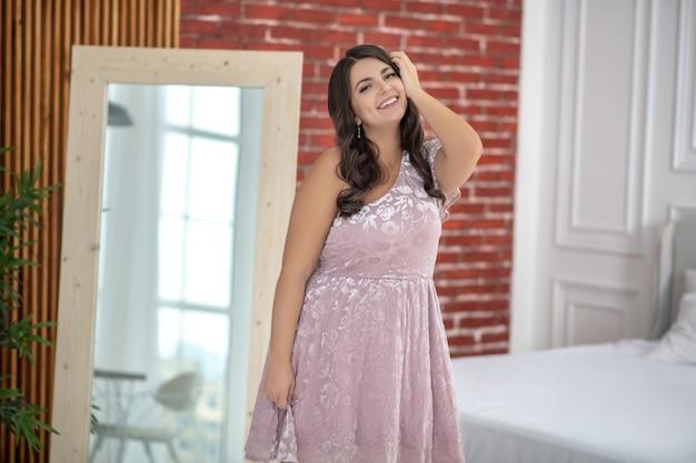 Młoda kobieta plus-size w różowej sukience czuje się świetnie