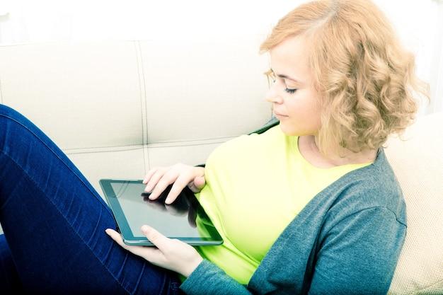 Młoda kobieta plus size z komputerem typu tablet spoczywającym na kanapie.