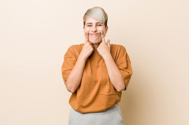 Młoda kobieta plus size z krótkimi włosami, która wątpi w dwie opcje.