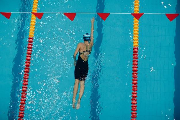Młoda kobieta pływak pływa w basenie