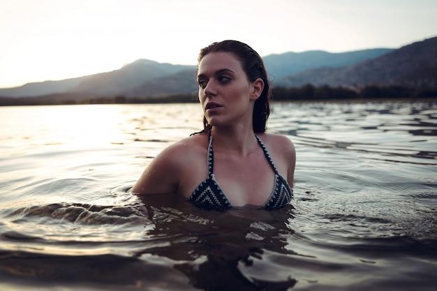 Młoda kobieta, pływanie w jeziorze o zachodzie słońca