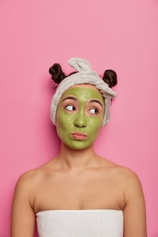 Młoda kobieta po kąpieli nosi naturalną maseczkę na twarz