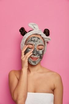 Młoda kobieta po kąpieli nosi naturalną maseczkę z glinki na twarz