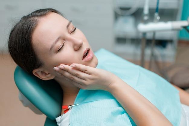 Młoda kobieta po leczeniu stomatologicznym w gabinecie stomatologicznym