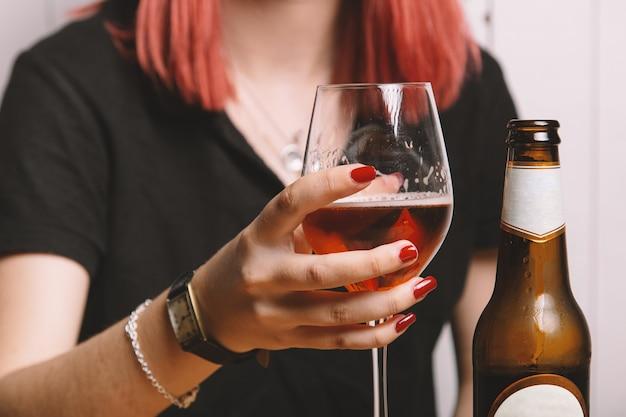 Młoda kobieta po szklance piwa. na białym tle obraz.