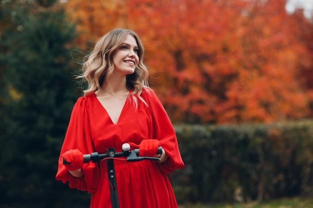 Młoda kobieta pobyt ze skuterem elektrycznym w czerwonej sukience i uśmiech w parku jesienią