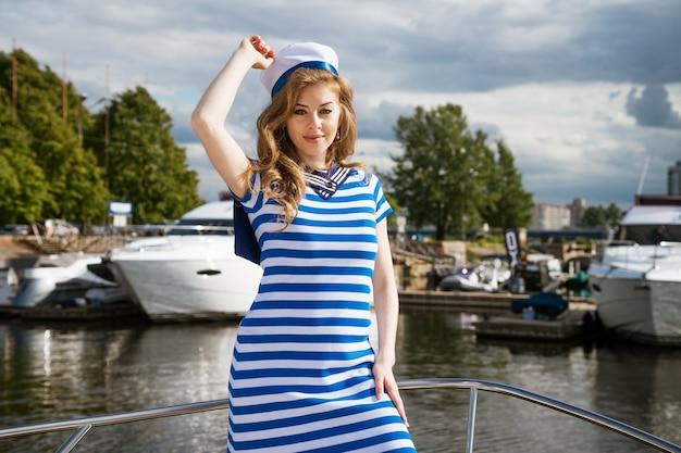 Młoda kobieta pochodzenia kaukaskiego w krótkiej sukience z niebieskimi paskami i czapką na jachcie pozowanie na słoneczny dzień koncepcji rozrywki wodnej