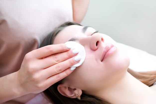 Młoda kobieta pociera oczy gąbką i wykonuje zabieg laminowania rzęs w salonie kosmetycznym, zbliżenie