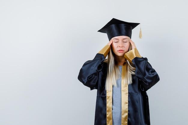 Młoda kobieta pociera skronie w mundurze absolwenta i wygląda na zmęczoną