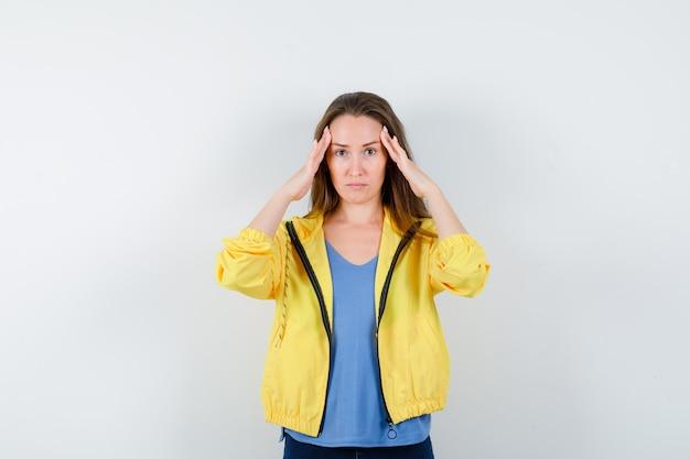 Młoda kobieta pociera skronie w t-shirt, kurtkę i wygląda na zmęczoną, widok z przodu.