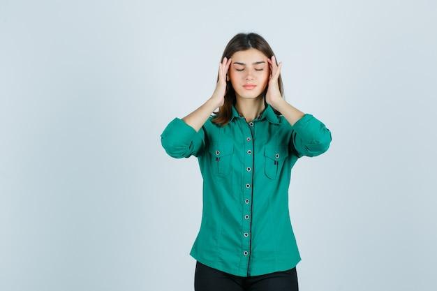 Młoda kobieta pociera skronie w zielonej koszuli i wygląda na zrelaksowaną. przedni widok.