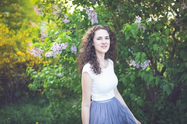 Młoda kobieta pod kwitnącym lilym drzewem