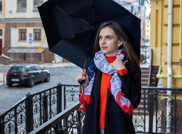 Młoda kobieta pod parasolem na ulicy miasta