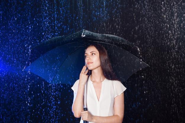 Młoda kobieta pod parasolem. ochrona przed deszczem.