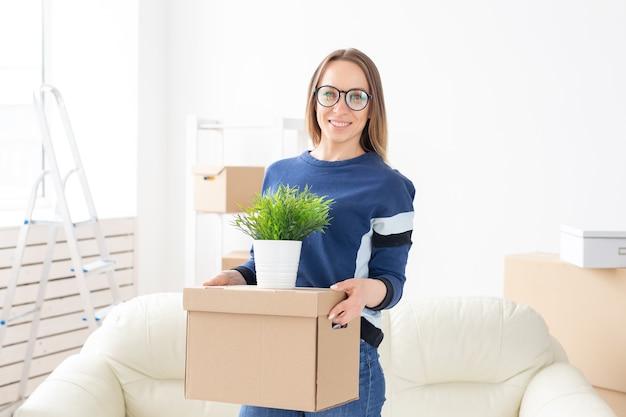 Młoda kobieta podczas przeprowadzki do nowego mieszkania trzyma pudełko i doniczkę z roślinami.
