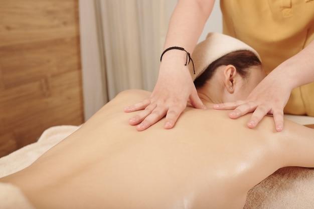 Młoda kobieta podczas relaksującego masażu pleców z olejkami w salonie spa