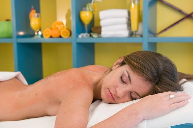 Młoda kobieta poddawana zabiegowi na ciało w miejscu masażu