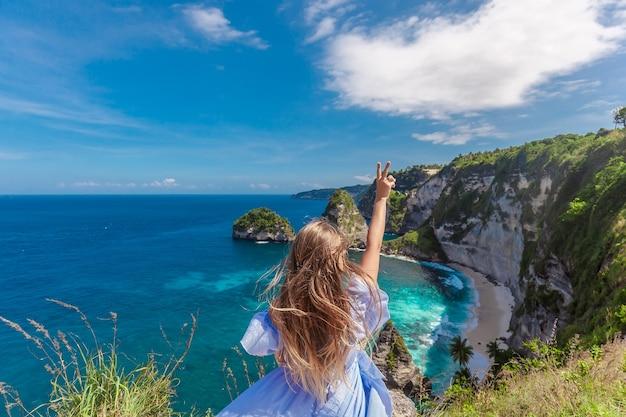 Młoda kobieta podniosła rękę w pięknym skalistym wybrzeżu na nusa penida
