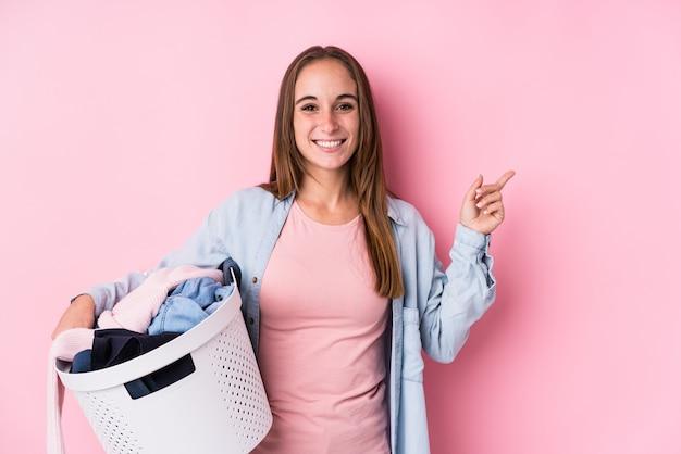 Młoda kobieta podnosi brudne ubrania uśmiecha się i wskazuje na bok, pokazując coś w pustej przestrzeni