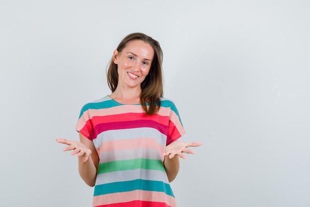 Młoda kobieta podnosi dłonie jako gest powitalny, w koszulce i wygląda na zadowoloną. przedni widok.